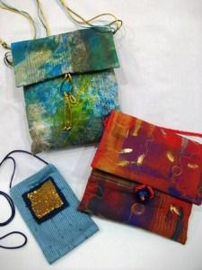 Large blue purse - handpainted fabric, glass bead closure. Red purse - hand painted fabric, glass bead closure. Small blue purse - commercial fabric, distressed plastic embellishment.